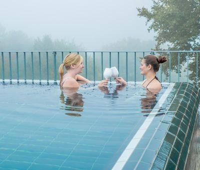 Zwei Damen stoßen im Wasser im Freibad mit Sekt an.