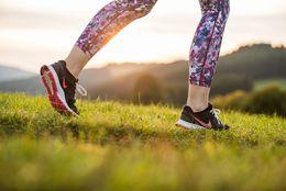 Detailansicht auf die bunte Sporthose und die Sportschuhe der Läuferin