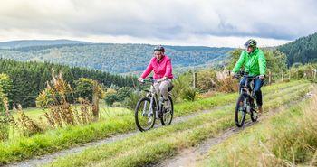 Ein Paar fährt auf E-Bikes über einen Feldweg. Im Hintergrund ist ein Wald.