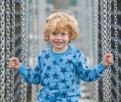 Ein kleiner junge hält sich auf der Panorama Brücke fest und strahlt über das ganze Gesicht
