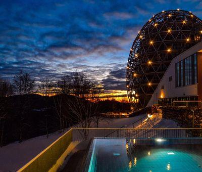 Freibad bei Dunkelheit mit beleuchtetem eiförmigen Hotel im Hintergrund
