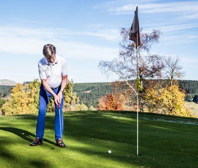 Golfer beim Abschlag, Ball liegt kurz vor dem Zielloch, im Hintergrund schöne Herbstlandschaft