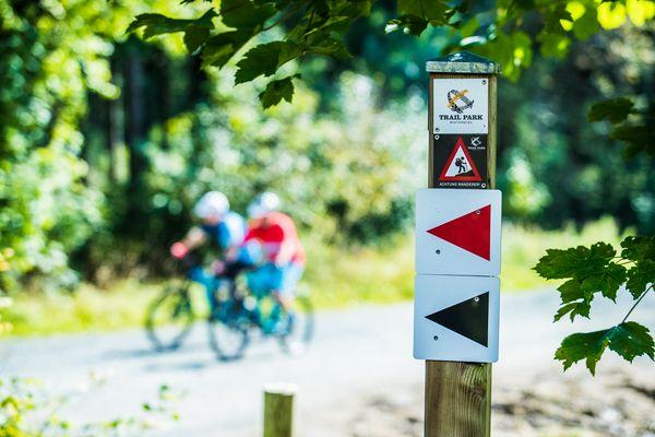 Säulen mit rotem und schwarzen Pfeil zur Beschilderung der Fahrradstrecken, im Hintergrund zwei Biker