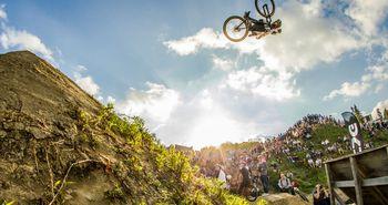 Biker zeigt bei einem Festival vor vielen Zuschauern einen spektakulären Sprung über eine Rampe