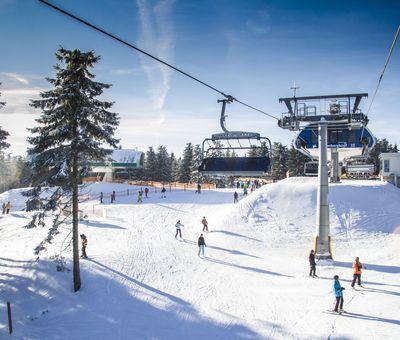 Der Blick auf den Sessellift im Skigebiet mit Skifahrern auf der Piste, Ansicht von oben