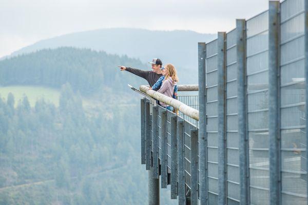 Familie steht auf einer Brücke, Mann zeigt mit dem Finger in eine Richtung