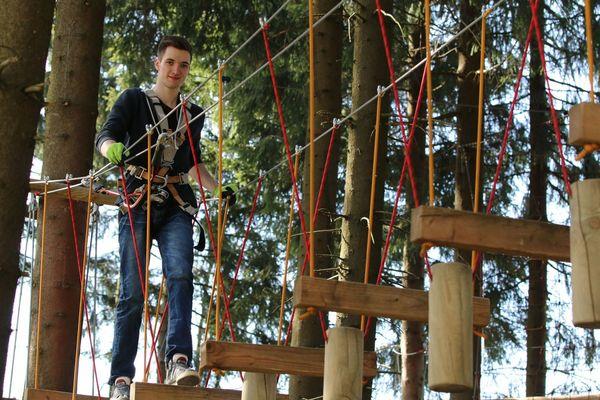Ein Mann klettert im Kletterwald am Erlebnisberg Kappe über in der Luft aufgehängte Balken