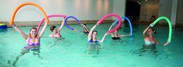 Eine Gruppe Frauen macht Aquagymnastik mit Schwimmbadnudeln