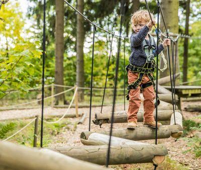 Ein kleiner Junge überwindet den Wackelpfad mit einzeln quer hängenden Baumstämmen
