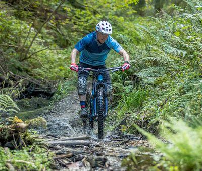 Ein Biker fährt schnell über einen schmalen Weg, der nass und steinig ist