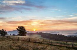 Sonnenaufgang mit Wiesen im Vordergrund und Bergen im Hintergrund