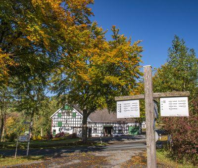 Fachwerkhaus mit Wegweiser und Herbstlaub