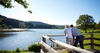 Zwei Personen blicken von einer Terrasse über einen idllyschen Bergsee