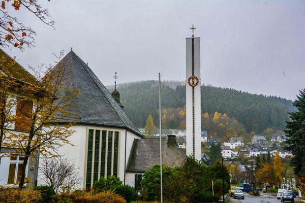 Dorf mit Kirche vor einem grünen Hügel