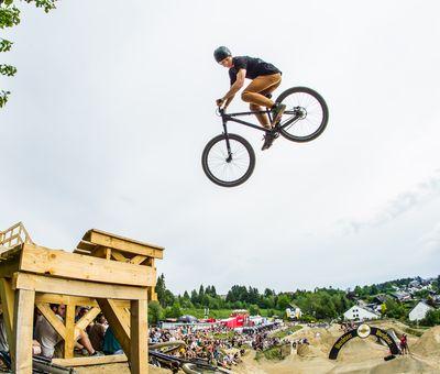 Ein Biker fliegt mit seinem Rad durch die Luft zur nächsten Plattform