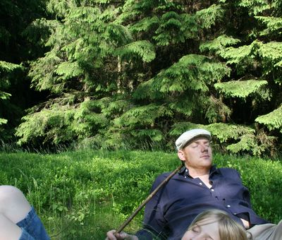 Familie liegt im Gras und macht eine Pause