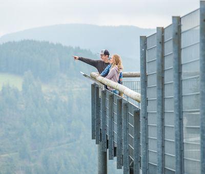 Ein Paar steht gemeinsam auf der Panorama Erlebnis Brücke und schaut und zeigt in die Ferne