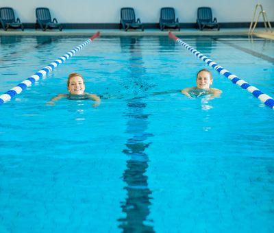 Zwei Personen schwimmen Bahnen in einem Sportbecken