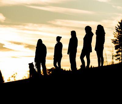 Fünf Frauen wandern mit ihrem Hund über eine Wiese. Man sieht nur Silhouetten der Personen. Im Hintergrund geht die Sonne unter.