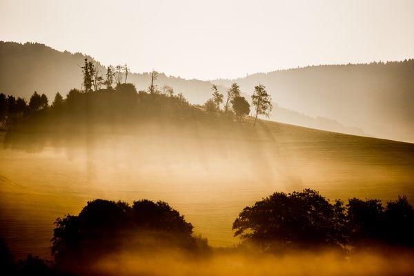 Eine hügelige Landschaft mit tiefem Nebel, der von der Sonne aufgehellt wird