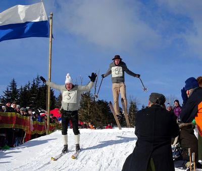 Zwei Teilnehmer des Nostalgieskirennens fahren einen Hügel hinunter. Am Rand stehen Zuschauer.
