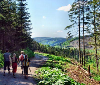 Eine Familie bei der Wanderung, dahinter Ausblick über die Landschaft