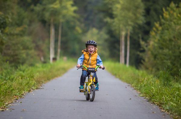 Ein kleiner Junge fährt mit seinem Fahrrad über einen asphaltierten Weg.