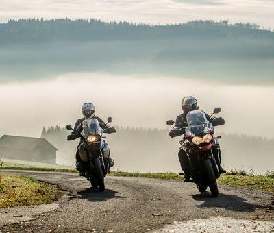 Zwei Motorradfahrer vor bergiger Landschaft im Nebel