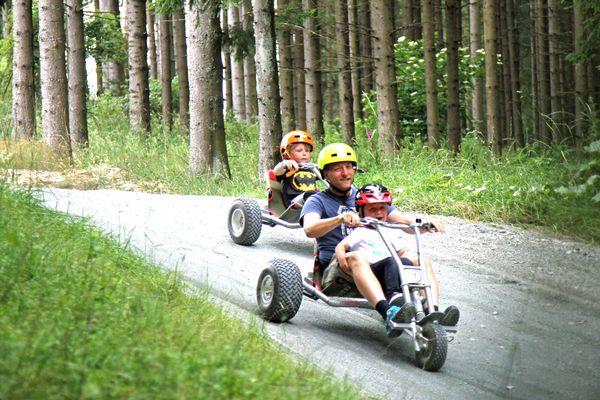 Zwei Jungs fahren mit Mountaincarts einen Berg hinunter