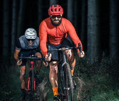 Zwei Biker fahren über einen schmalen Weg, die Matsche wird vom Rad hochgeschleudert