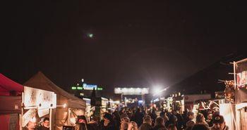 Festival bei Nacht, Stände an den Seiten und im Gang dazwischen laufen die Besucher