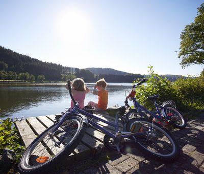 Zwei Kinder sitzen auf einem Steg am Wasser, im Vordergrund die Fahrräder