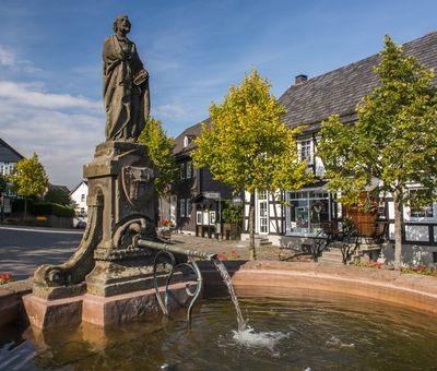 Ortsmitte von Hallenberg mit dem Petrusbrunnen. Im Hintergrund stehen mehrere Fachwerkhäuser.