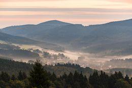 Der Ort liegt im Tal und ist von Nebelschwaden umhüllt