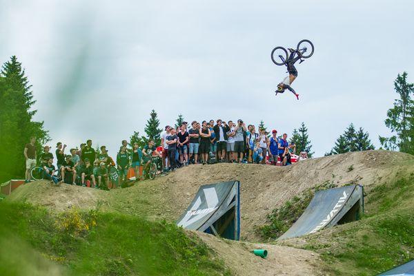 Im Hintergrund stehen die Zuschauer, im Vordergrund macht ein Biker kopfüber einen Stunt