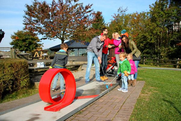 Eine Familie spielt am Erlebnisberg Kappe Minigolf