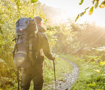 Wanderer mit Rucksack und Stöcken, Bildaufnahme von hinten