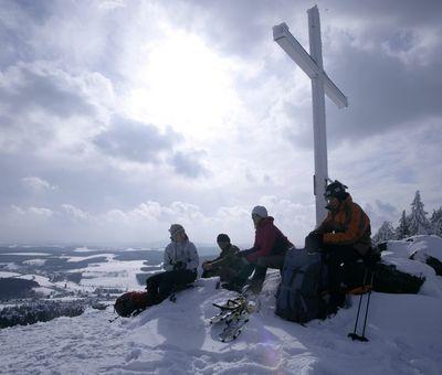 Eine Gruppe Winterwanderer sitzt bei Schnee an einem Gipfelkreuz und genießt die Aussicht