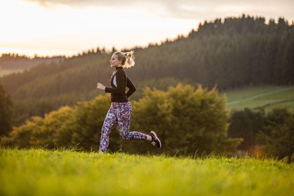 Eine Läuferin bei Sonnenaufgang auf einer Wiese in der Ferienwelt Winterberg