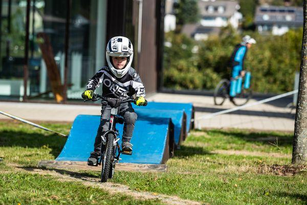 Ein kleiner Junge fährt bei den Bike Games mit seinem Fahrrad durch den Kinderparcours