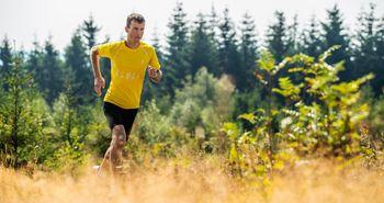 Ein Mann läuft durch die Natur. Im Hintergrund ist ein Wald.