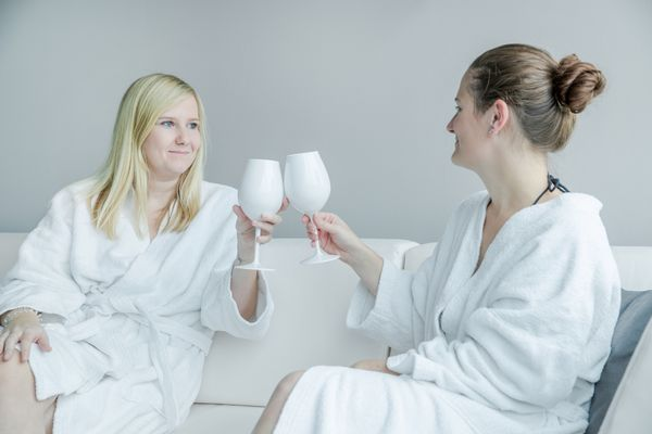 Zwei Freundinnen im Bademantel stoßen miteinander an