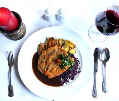 Das Gericht serviert auf weißem Geschirr, links eine Kerze, rechts ein Rotweinglas