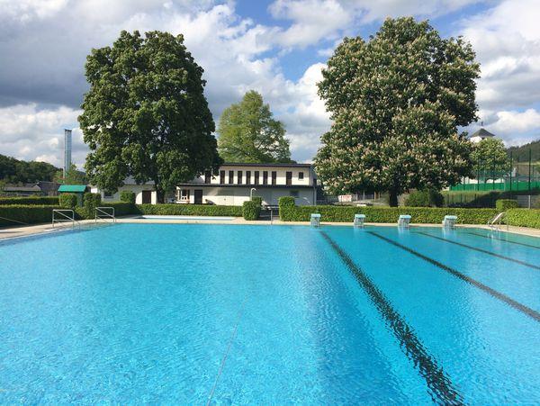 Schwimmbecken des Freibads in Siedlinghausen. Im Hintergrund ein Gebäude zwischen Bäumen.
