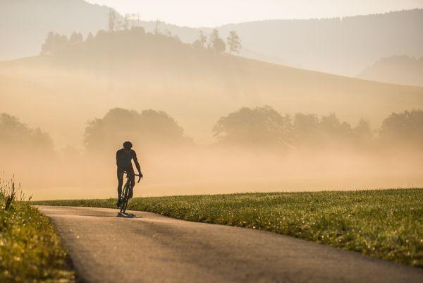 Biker fährt eine asphaltierte Straße hoch, die Landschaft ist mit Nebel bedeckt