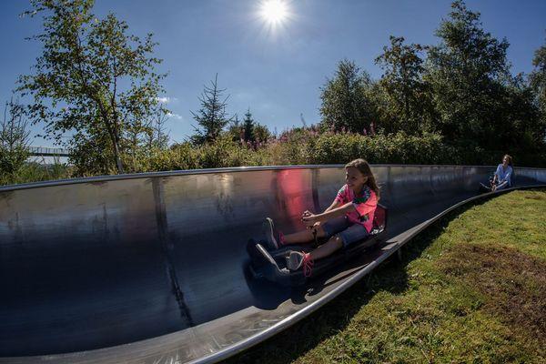 Eine Familie fährt mit der Sommerrodelbahn am Erlebnisberg Kappe