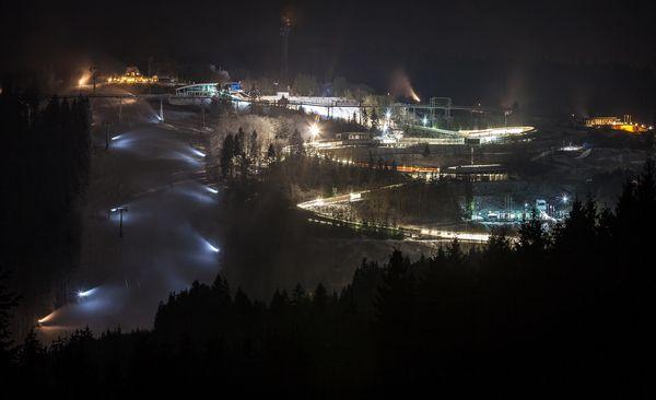 Ansicht von oben, Blick auf die Bobbahn, die mit Flutlicht ausgeleuchtet ist