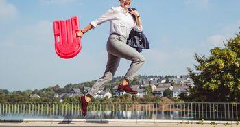 Eine Frau spring mit einer roten Tasche in der Hand vor einem Schwimmbecken entlang