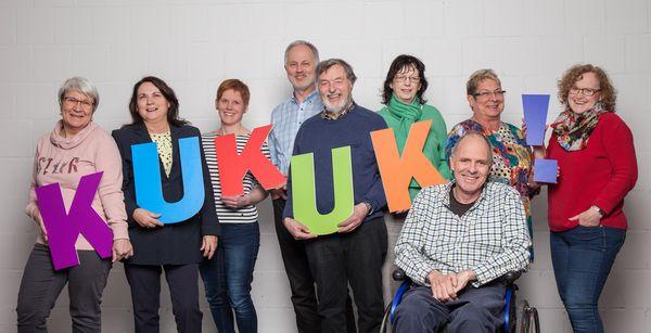 Das KuKuKu-Team steht vor einer weißen Wand und bildet mit bunten Buchstaben das Wort KuKuK