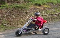 Ein Kind fährt auf einem Mountaincart einen Weg hinunter
